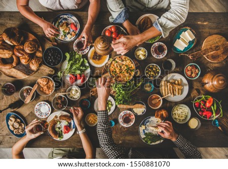 Turkish breakfast. Flat-lay of family eating pastry, vegetables, greens, cheeses, fried eggs, jams from oriental tableware and drinking tea from tulip glasses over rustic wooden background, top view
