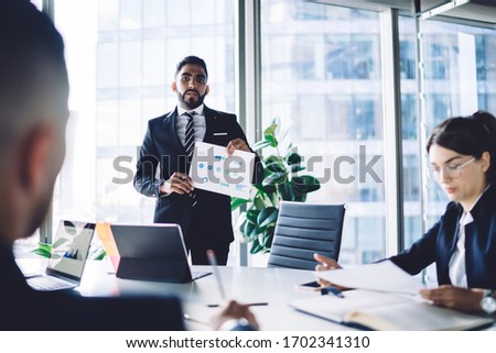 Turkish businessman making training conference meeting with male and female employees explaining statistic information from corporate report, group of experienced people discussing strategy teamwork