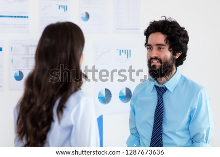 Turkish businessman talking with businesswoman about strategy at office of company