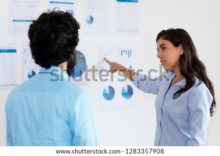 Turkish businesswoman talking with businessman about strategy at office of company