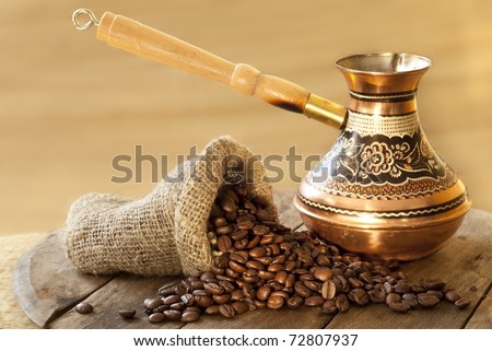 Turkish coffee in a copper Turks and grains are scattered on the wooden surface