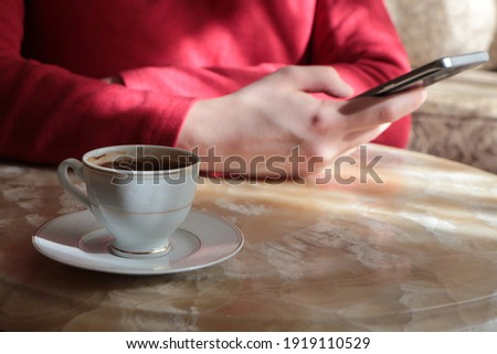 Turkish coffee on table and woman holding phone who wear a red sweater.Cropped image young woman sitting at the table with cup of coffee and smart phone,woman's hand typing message on touch screen.  Foto stock ©