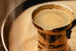 Turkish coffee prepared in sand with turk