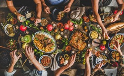 Turkish cuisine family feast. Flat-lay of people celebrating with lamb chops, quince, bean, salad, babaganush, rice pilav, pumpkin dessert, lemonade over rustic table, top view. Middle East cuisine
