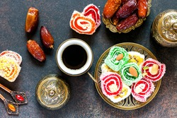Turkish delight, coffee and dates against a dark background. Top view.