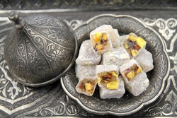 Turkish delight ( lokum or rahat lokum ) with pistachio nuts in traditional carved patterned metal plate