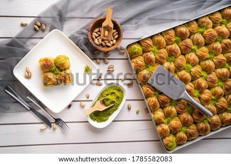 Turkish desert baklava with peanut,  pistachio, hand on fork and Turkish tea for Turkish holiday or ramadan holiday, midye baklava
