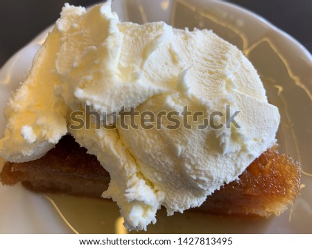 "Turkish desserts are well-known around the world in their own right. There is ""ekmek kadayifi"" dessert in the photo. This dessert served with cream. #1427813495"