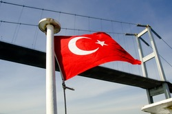 Turkish flag flutter in the wind in front of the bridge with blue sky in background