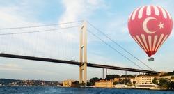 Turkish flag Hot air balloon flying over Istanbul bridge Bosporus - Travel concept.