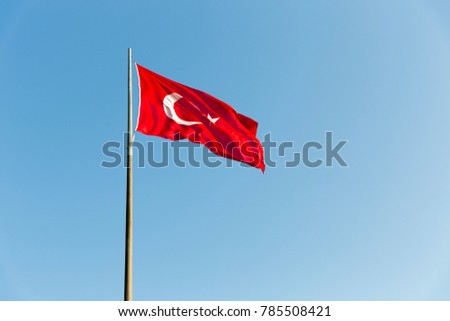 Turkish flag on long metal iron pole waving in blue sky. Red flag featuring a white star and crescent. Flag is often called al bayrak  and is referred to as al sancak in the Turkish national anthem. #785508421