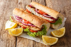 Turkish food sandwich balik Ekmek with grilled mackerel, tomatoes, onions and lettuce served with lemon closeup on the table. horizontal