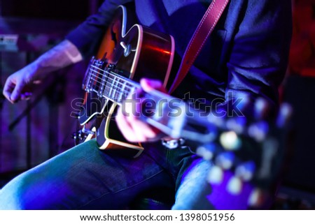 Turkish guitarist and great artist is playing his beloved musical instrument in a dark studio. He is lightened with blue and purple lights from the front and above. Close up guitar photo.