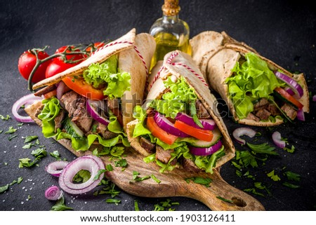 Turkish kebab wrap shawarma  sandwiches. Tasty fresh wrap sandwiches with beef meat and vegetables, Traditional Middle Eastern snack.