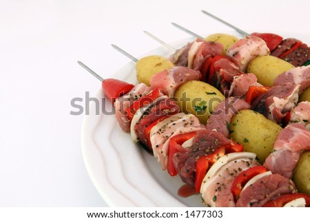 Turkish kebabs with beef, lamb, pork, onion, red and green peppers, with spicy herb potatoes on skewers, on white, copy space, macro, close up
