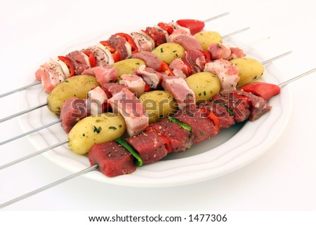 Turkish kebabs with beef, lamb, pork, onion, red and green peppers, with spicy herb potatoes on skewers, isolated on white, copy space