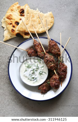 Turkish Kofta on an enamel plate with dill yogurt dip