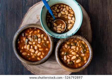 Turkish Kuru Fasulye / Baked Beans in a wooden bowl.