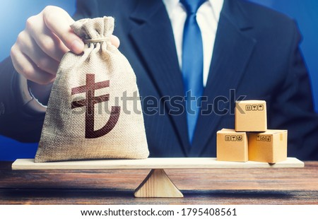 Turkish lira money bag and boxes on scales. Trade balance and purchasing power. Economic and industrial development. Import and export duties, profit from the sale of value added goods. VAT Foto stock ©