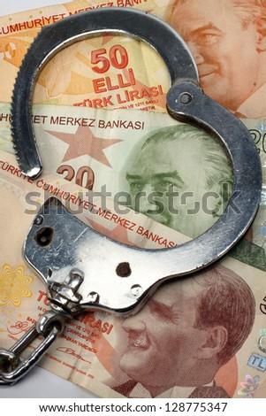Turkish liras bills and handcuffs close up. Financial Crime and Corruption