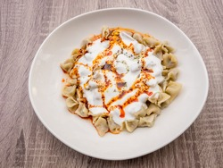 Turkish Manti with red pepper, tomato sauce, yogurt and mint. Plate of traditional Turkish food