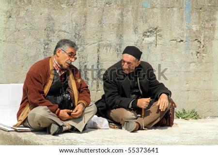 Turkish men chatting sitting at a wall