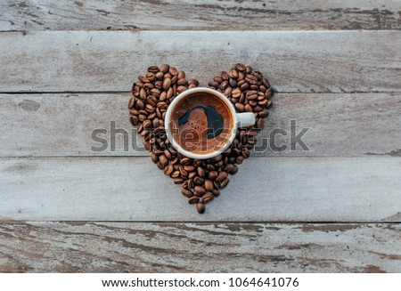 Turkish or Greek Coffee in heart shaped roasted coffee beans on white rustic wooden table from top view. Traditional tasty refreshment greek or turkish coffee from greek or turkish cuisine culture