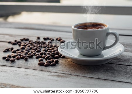 Turkish or Greek Hot Coffee on the white rustic wooden table with spilled coffee beans. This is traditional tasty refreshment greek or turkish coffee from greek or turkish cuisine culture