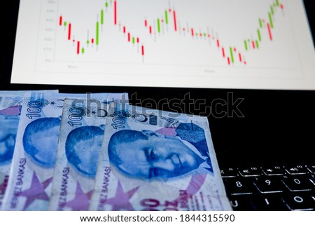 Turkish paper money and coins tower in office. Stock exchange market concept, Business investor trading or stock brokers having a planning and analyzing with display screen, Turkish Lira.