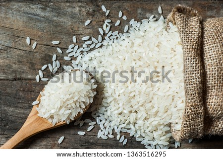 turkish raw white rice grains with burlap sack in wooden spoon on wooden background, healthy food uncooked legumes concept