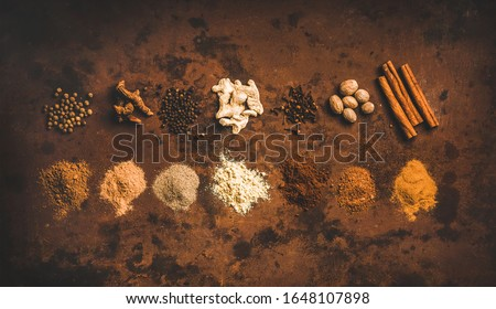 Turkish seven spice Yedi Bahar mix. Flat-lay of black pepper, ginger, cloves, nutmeg, cinnamon, allspice and alpinia root over rusty background, top view, horizontal compotision Stok fotoğraf ©
