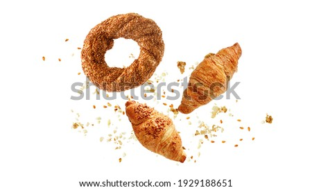 Turkish simit sesame bagel, french butter and almond nut croissants flying with crumbs isolated on white background.