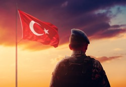 Turkish Soldier is stand and salute front of Turkish Flag on his watch duty.