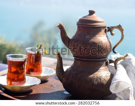 Turkish tea with authentic glass cup and copper tea kettles. Two cups of turkish tea served in traditional style with view on Bosporus. Istanbul cafe with oriental culture of the street food.