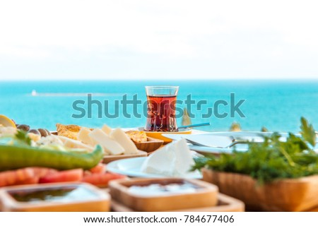 Turkish tea with breakfast on the table in front of sea background landscape at Summer season. Turkish or Greek Breakfast at seaside. This turkish tea is red. Holiday and vacation in Turkey or Greece