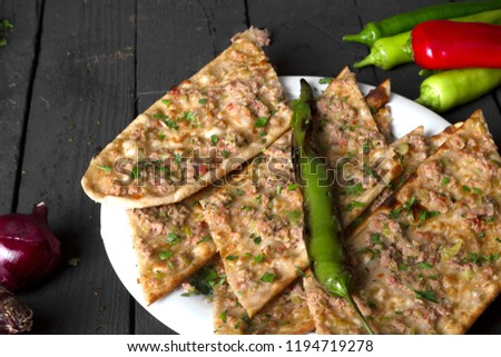 Turkish Traditional Ramadan Pide Kebab Etli Ekmek with roasted pepper, tomato and onion on rustic black wooden table background. Dark photography concept.