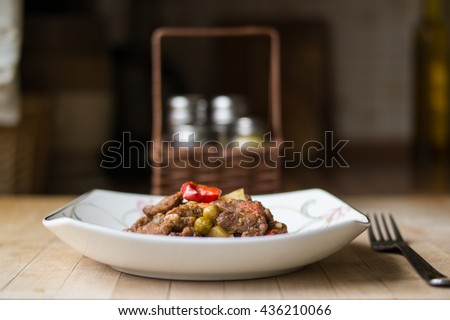 Turkish traditional tas kebab with potato, pea and tomato in a white plate on a wooden surface at home in the kitchen front view