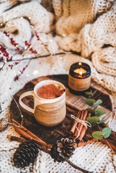 Turkish traditional wintertime hot drink Salep. Mug of sweet warming Salep drink with ground cinnamon on tray over knitted blanket. Turkish seasonal cuisine, Christmas and New Year mood