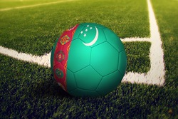 Turkmenistan flag on ball at corner kick position, soccer field background. National football theme on green grass.