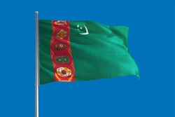 Turkmenistan national flag waving in the wind on a deep blue sky. High quality fabric. International relations concept.