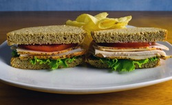 turky sanwich between wheat breat and a side of chips,