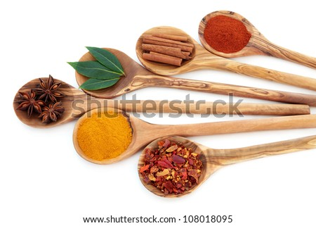 Turmeric, bay leaf herb, chili flakes, star anise, cinnamon sticks and cayenne pepper spice in olive wood spoons over white background.