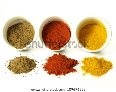 Turmeric, cumin and hot pepper on isolated background