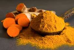 Turmeric (curcumin) powder in a wooden ladle and fresh rhizome on a black background,For spices and medicine.