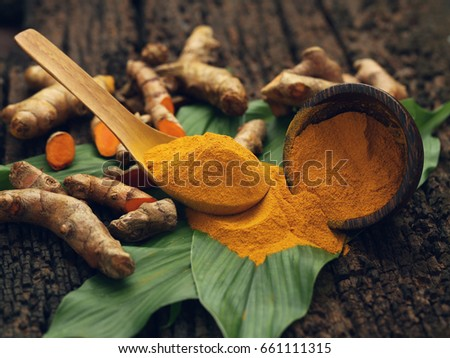 Shutterstock Turmeric powder and fresh turmeric on wooden background.
