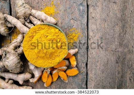 Shutterstock Turmeric powder and turmeric on wooden background .- Vintage Filter Processing.