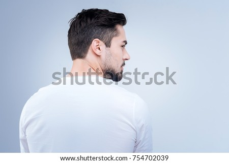 Turn back. Quiet calm serious man waiting for his friend while sitting against the blue background and looking to the right