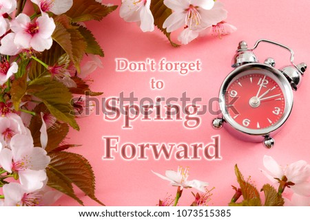Turn clocks one hour ahead, start of daylight savings time change and reminder to spring forward concept with clock on pink background with springtime flowers and text - Don't forget to spring forward