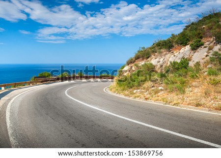 Turn of mountain asphalt road with blue sky and sea on a background