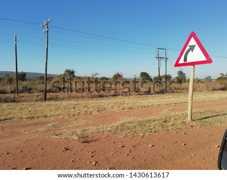 Turn signs next to side of the road.. Dirt road effect #1430613617